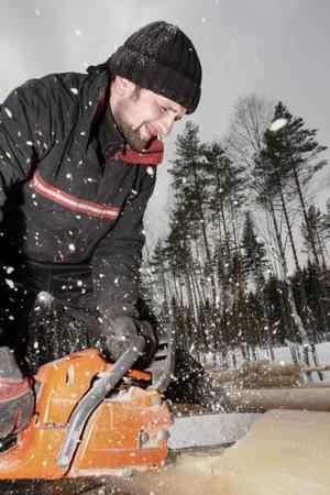 Leningrad Region, Russland - 2. Februar 2010: Bauarbeiter trimmen ein Protokoll mit einer Kettensäge, das Sägemehl fliegen.