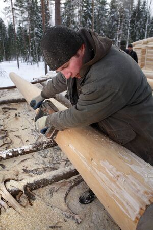 planos electricos: Leningrad Region, Russia - February 2, 2010: Woodworker Planes timber, using an electric planer. Editorial