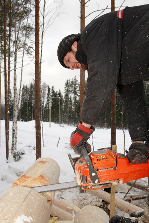 notch: Leningrad Region, Russia - February 2, 2010: Corner notch, cutting and brushing for log cabin construction, using chainsaw.