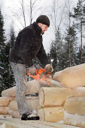 Leningrad Region, Russia - February 2, 2010: Construction of log house, a young worker sawed timber, using a chainsaw.