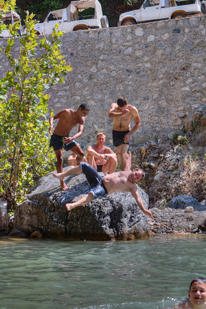 Kemer, Antalya, Turkey - august 26, 2014: Vacationers have fun near the mountain river, two tourists thrown into the water his friend. Editorial