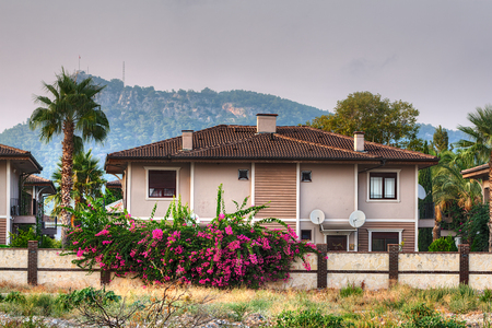 Camyuva, Kemer, Antalya, Turkey - 28 august, 2014: two-storey villa surrounded by palm trees and flowering bushes against the backdrop of forested mountains in the village of Camyuva Resort.