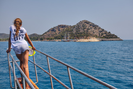 Antalya, Turkey - 28 august, 2014: One unknown teenager girl looks towards the harbor, standing on the nose of a sightseeing boat.