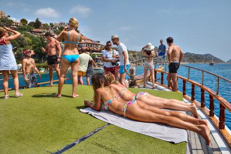 insolación: Antalya, Turquía - 28 de agosto de 2014: Los turistas a bordo de viaje en barco de ocio, los pasajeros obtener bronceado y fotografiado.