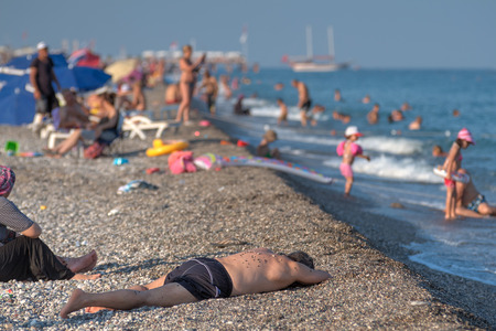 Antalya, Turkey - 25 august, 2014: The beach on the shore of the Mediterranean Sea, the man is dozing, lying on the gravel.