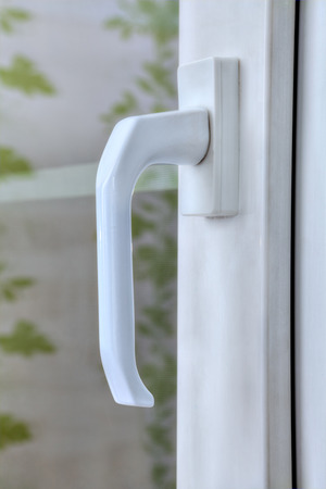 Close-up handle of the pvc window locking mechanism with double glazing.