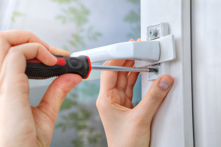 dismantle: Unscrewing the screw handles plastic window with a hand tool. Stock Photo