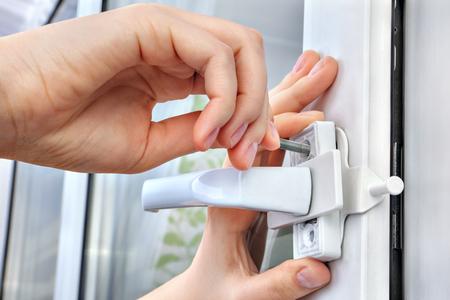 De slotenmaker installeert restrictor voor een plastic venster, schroefde hij schroef gebruikend zijn vingers, close-up.