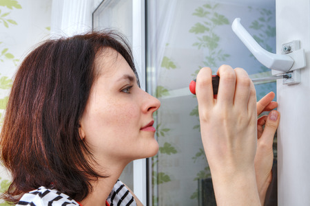 dismantle: Young woman unscrews the fixing screws of the window handle.