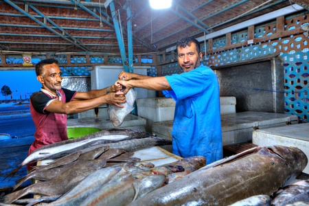 fish vendor: Bandar Abbas, Hormozgan Province, Iran - 15 april, 2017: Iranian fishmonger passes assistant fresh flounder on the covered fish market. Editorial
