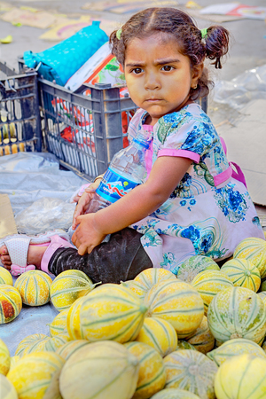 petite fille musulmane: Bandar Abbas, Hormozgan Province, Iran - 16 april, 2017: One unknown little girl, about three years old, sits outside the eastern bazaar, on the sidewalk near the melons, just editorial use. Éditoriale