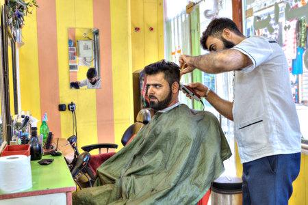 Bandar Abbas, Hormozgan Province, Iran - 16 april, 2017: Iranian hairdresser, Persian hairdresser makes a hairdo for a man. Editorial