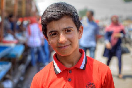 Bandar Abbas, Hormozgan Province, Iran - 16 april, 2017: One unknown Persian youth, about 14 years old, in an orange shirt, a close-up portrait against a city street background.