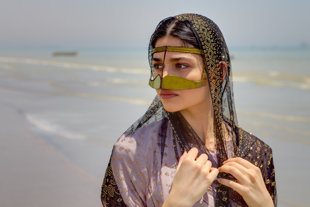 Bandar Abbas, Hormozgan Province, Iran - 16 april, 2017: Traditional costume of southern Iran, beautiful young woman wearing a mask and hijab, walking along shore of Persian Gulf, a close-up portrait.