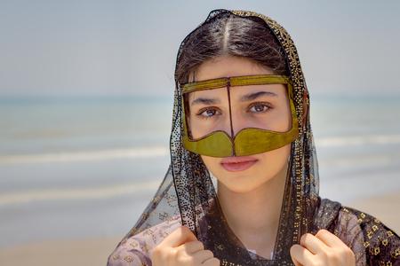 Young bandari woman wearing a traditional mask called the burqa, Coast of the Persian Gulf near the city of Bandar Abbas, Hormozgan province, southern Iran. Фото со стока