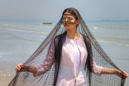 Bandari woman wears a traditional mask, beach of Persian Gulf, Hormozgan province, southern Iran.
