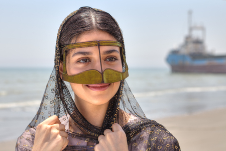 Young Iranian woman in traditional mask of Muslim women in southern Iran, smiling, standing on the shore of the Persian Gulf in Hormozgan province, close-up portrait.