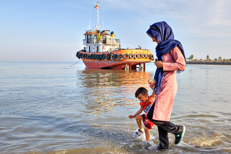 Bandar Abbas, Hormozgan Province, Iran - 16 april, 2017: A woman in a hijab leads a little boy by the hand, walks through the shallow waters of the Persian Gulf on a sunny evening.
