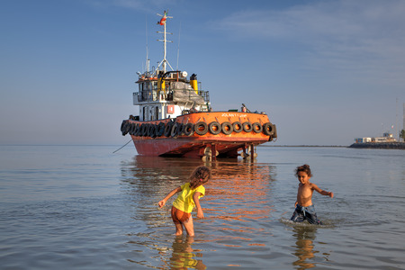 shallow: Bandar Abbas, Hormozgan Province, Iran - 16 april, 2017: Two little girls, about seven years old, play in the water near the shore, against the background of an industrial boat that ran aground.