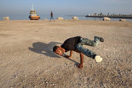 bailarinas arabes: Bandar Abbas, provincia de Hormozgan, Irán - 16 de abril de 2017: El joven iraní muestra una figura, un breakdance en la playa del Golfo Pérsico.