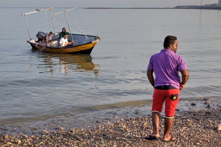 provinces: Bandar Abbas, Hormozgan Province, Iran - 16 april, 2017: An Iranian man is standing on the shore to which a pleasure boat with four people aboard is arriving. Editorial