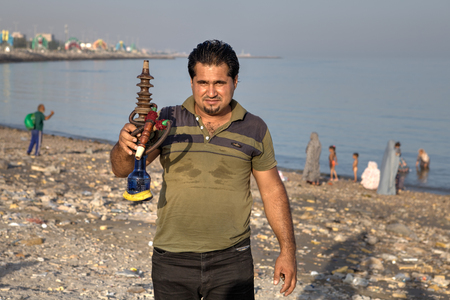provinces: Bandar Abbas, Hormozgan Province, Iran - 16 april, 2017: One unknown Iranian man shows a hookah on the beach of the Persian Gulf. Editorial