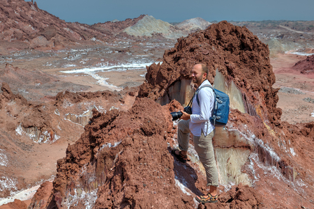 Hormuz Island, Hormozgan Province, Iran  - Tourist hike up the steep track on salty mountains, one backpacker admiring the beautiful scenery with a backpack and a camera. Stock Photo