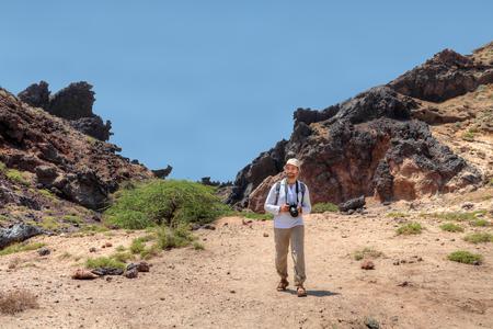 イランのペルシャ湾のホルムズ島、カメラとバックパックの中年の男性観光客は山道に行きます。