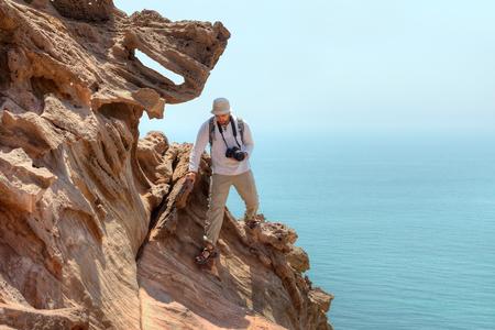 写真家の旅行者は、ホルモズガーン州、イランのホルムズ島、海の上の崖を登っていきます。 写真素材