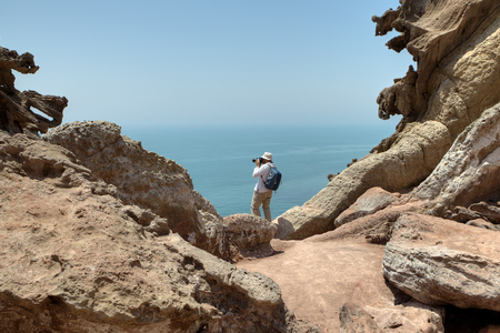 Tourist photographing nature, standing on the edge of a cliff., Iranian Island of Hormuz in Persian Gulf, Hormozgan Province, southern Iran.