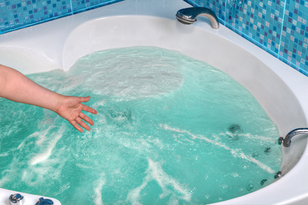 Close-up of a female hand checks the water temperature in the whirlpool hot tub.