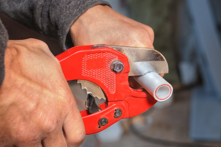 Close-up of a hand plumber using a cutter for plastic pipes.