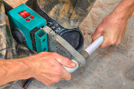 plastic conduit: Plumber installing pipes in home, ppr plastic pipe hot melt welding machine close-up.