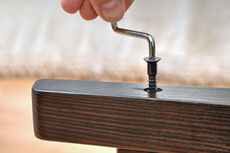 Assembly furniture at home, build a wooden chair using hex key, close up.