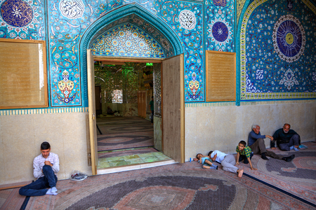 Fars Province, Shiraz, Iran - 18 april, 2017:  Mirrored mausoleum and Mosque of Sayyed Alaeddin Hossein, Muslim parishioners sit in front of the entrance.