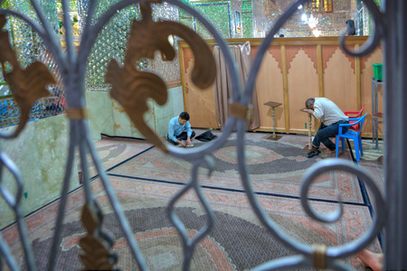 Fars Province, Shiraz, Iran - 18 april, 2017:  Muslim Shiite Men praying inside mirrored  Mosque of Sayyed Alaeddin Hossein.