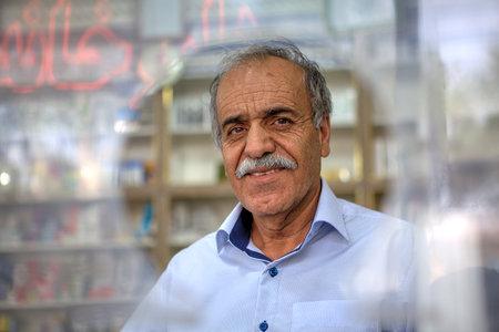 Fars Province, Shiraz, Iran - 18 april, 2017: Elderly man standing in front of round window on city street. Reklamní fotografie - 85797004