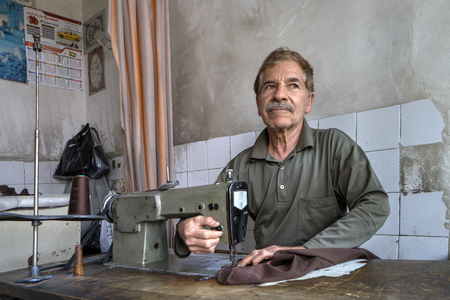 sewing machines: Fars Province, Shiraz, Iran - 18 april, 2017: An elderly tailor man in a tailors shop sews, using a sewing machine.