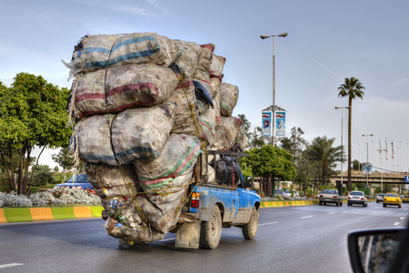 Fars Province, Shiraz, Iran - 18 april, 2017: Overloaded with sacks of household waste, the car is moving along the city road. Редакционное