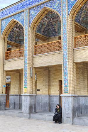 Fars Province, Shiraz, Iran - 19 april, 2017: Shah Cheragh mosque, one unknown Muslim woman in an Islamic veil, talking on the phone, sitting on the stone floor.