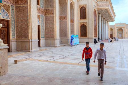 Fars Province, Shiraz, Iran - 19 april, 2017: Shah Cheragh Shrine, Two Iranian teenagers cross the courtyard of the mosque. Editöryel