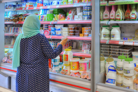 Fars Province, Shiraz, Iran - 20 april, 2017: One unknown elderly Muslim woman chooses food products on a shelf in a supermarket.