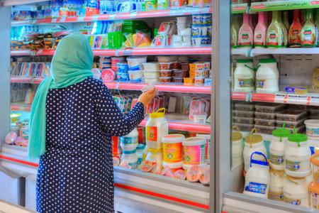 Provincia de Fars, Shiraz, Irán - 20 de abril de 2017: Una mujer musulmán mayor desconocida elige productos alimenticios en un estante en un supermercado.