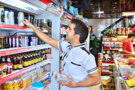 Fars Province, Shiraz, Iran - 20 april, 2017:  An adult Iranian man takes non-alcoholic beer on a shelf in a supermarket because alcoholic beverages are not sold in the Islamic republic.