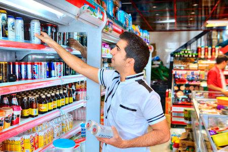 Província de Fars, Shiraz, Irã - 20 de abril de 2017: Um homem iraniano adulto toma cerveja não alcoólica em uma prateleira em um supermercado porque as bebidas alcoólicas não são vendidas na república islâmica.