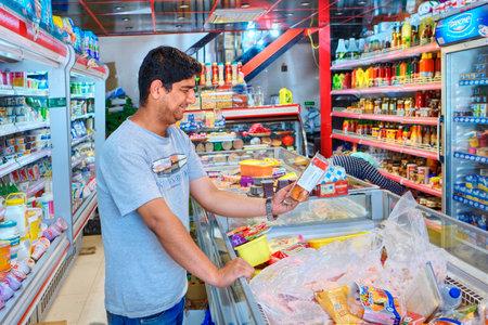 Provincia de Fars, Shiraz, Irán - 20 de abril de 2017: El comprador iraní observa el envase con comida en el supermercado. Editorial