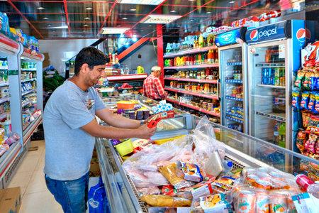 Provincia de Fars, Shiraz, Irán - 20 de abril de 2017: El comprador iraní observa el envase con comida en el supermercado.