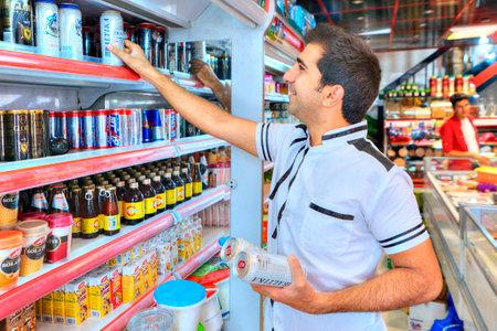 Provincia de Fars, Shiraz, Irán - 20 de abril de 2017: un hombre iraní maduro toma cerveza sin alcohol de un estante en un supermercado debido a la ley islámica, está prohibido beber alcohol.