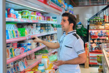 Provincia de Fars, Shiraz, Irán - 20 de abril de 2017: Un hombre iraní de mediana edad desconocido considera los productos comestibles en el estante de la tienda de comestibles.
