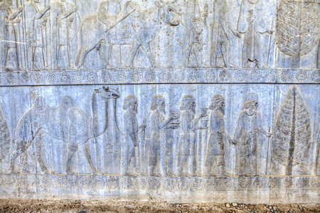 Slaves and soldiers carry gifts for Persian Emperor in Xerxes palace, stone bas-relief in ancient city Persepolis, Iran.